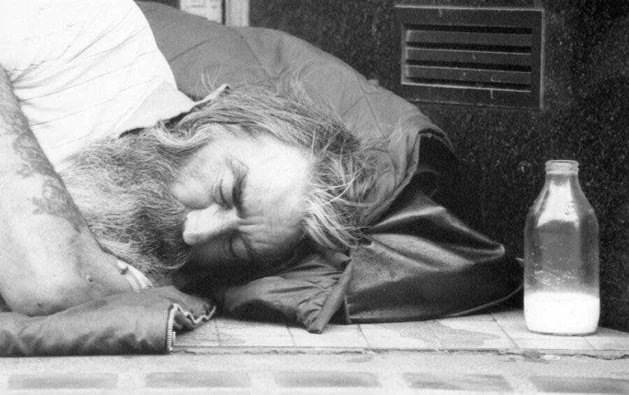 Il sonno di un homeless per strada.  Barbone. Senza fissa dimora. Solitudine. Alcol.  Disoccupazione.